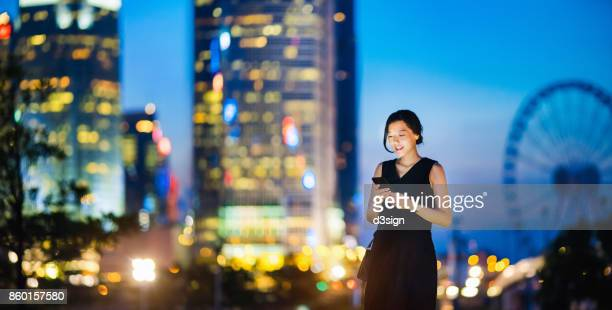 Beautiful young lady using smartphone in financial district at night, standing against modern corporate buildings