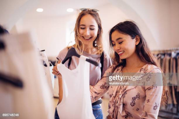 Beautiful young multi-ethnic women shopping in a boutique for clothes