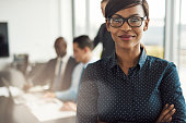 Beautiful young grinning professional Black woman in office with eyeglasses, folded arms and confident expression as other workers hold a meeting in background