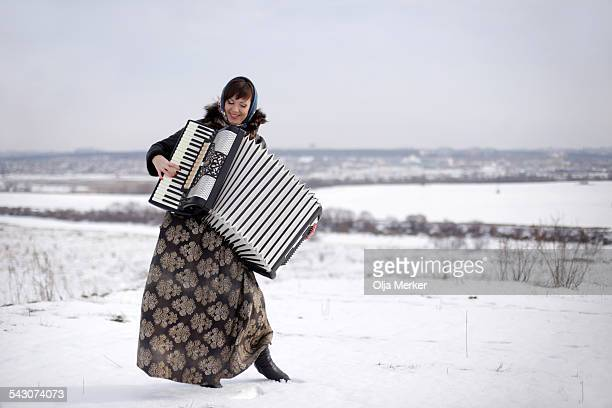 Beautiful young Russian woman playing an accordion
