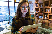 Portrait of beautiful young saleswoman using her digital tablet in organic shop.