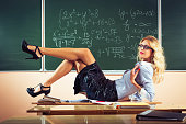 Beautiful young sexy teacher posing on table
