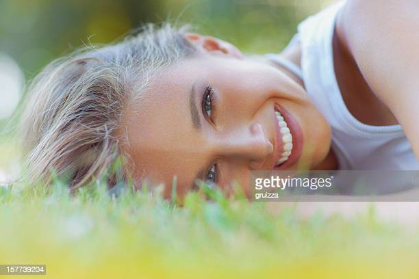 Beautiful, young, smiling, blonde woman laying on the grass