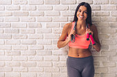 Beautiful young sportswoman in sportswear is holding a jumping rope, looking at camera and smiling, on white brick wall background