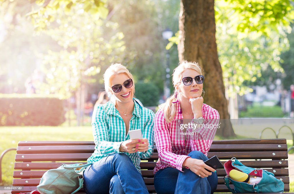 Beautiful young twins sisters in a summer green park : Stockfoto
