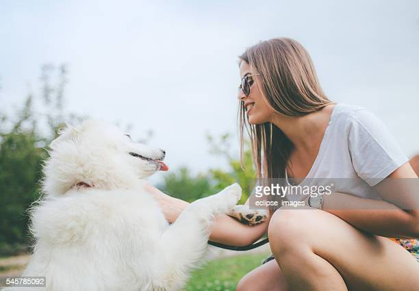 beautiful young woman and her dog enjoying in the nature