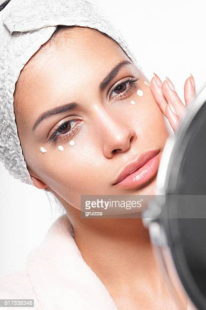 Beautiful young woman applying cream to her superb healthy skin