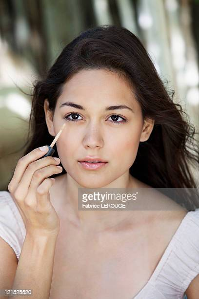 Beautiful young woman applying make-up