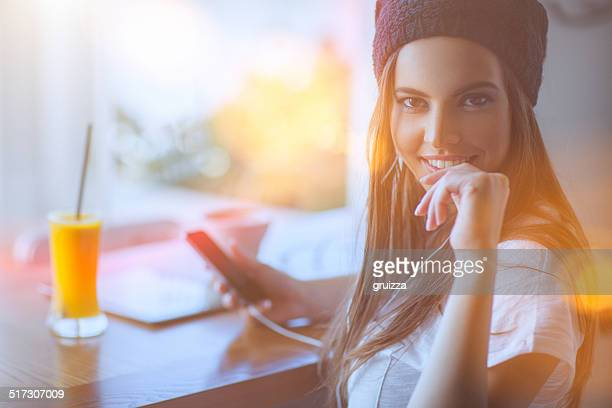 Beautiful young woman at cafe, using mobile phone