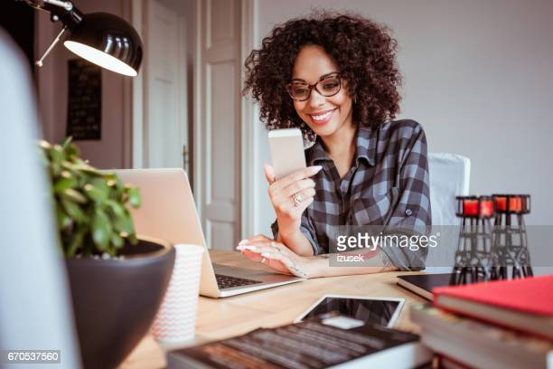 Beautiful young woman at office using mobile phone
