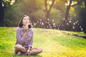 beautiful young woman sitting in the ground park and blowing bubble i