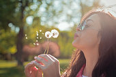 Beautiful young woman blowing dandelion in the park on a sunny day