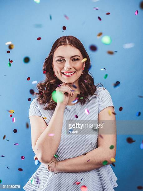 Beautiful young woman celebrating with confetti