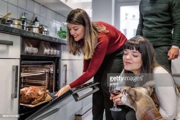 schöne junge Frau, die Überprüfung Weihnachten Geflügel im Backofen