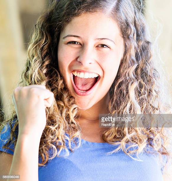 Beautiful young woman cheers, waving clenched fist