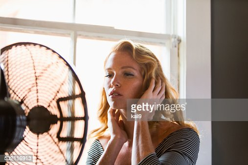 Beautiful young woman cooling off by fan