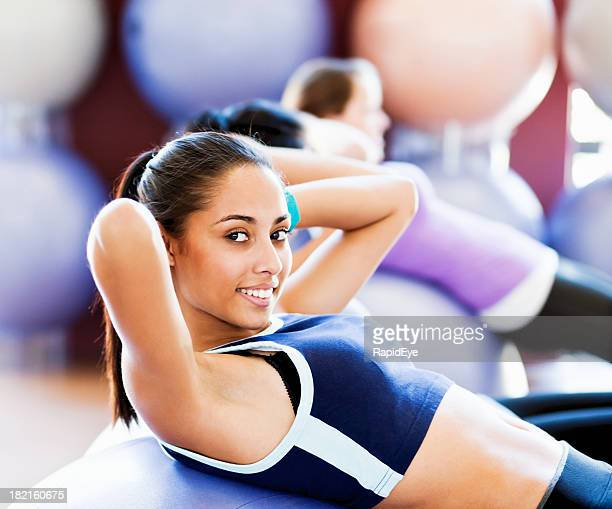 Beautiful young woman doing sit-ups smiles