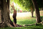 Beautiful young woman  doing yoga exercise on green grass in the park, supported headstand.