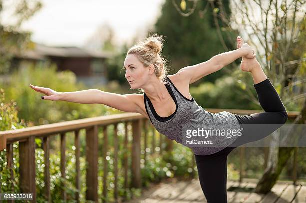 Beautiful young woman doing yoga on back porch