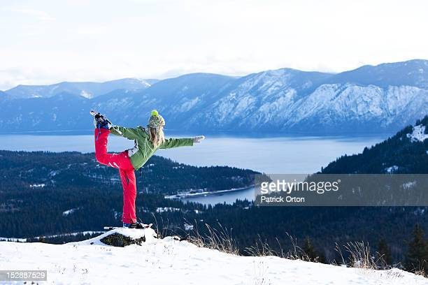 A beautiful young woman doing yoga while snowshoeing above a lake in Idaho.