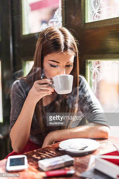 Beautiful young woman drinking coffee in a cafe.