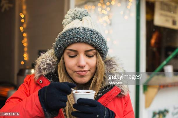 Beautiful young woman drinking hot chocolate on the street