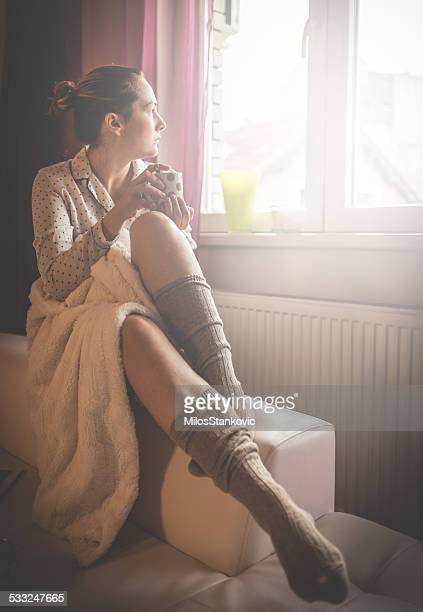 Beautiful young woman drinking morning coffee by the window