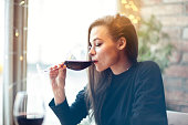 Beautiful young woman drinking red wine with friends in cafe, portrait with wine glass near window. Vocation holidays evening concept