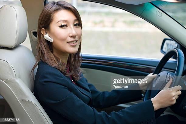Schöne Junge Frau mit dem Auto reden auf den Kopfhörer