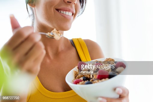 Beautiful young woman eating cereals and fruits at home. : Stock Photo