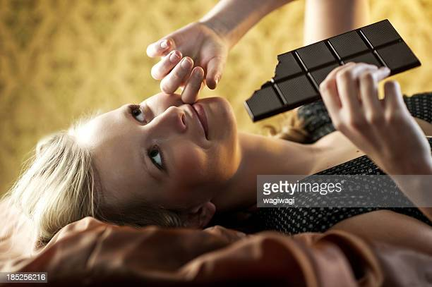 Beautiful young woman eating chocolates.