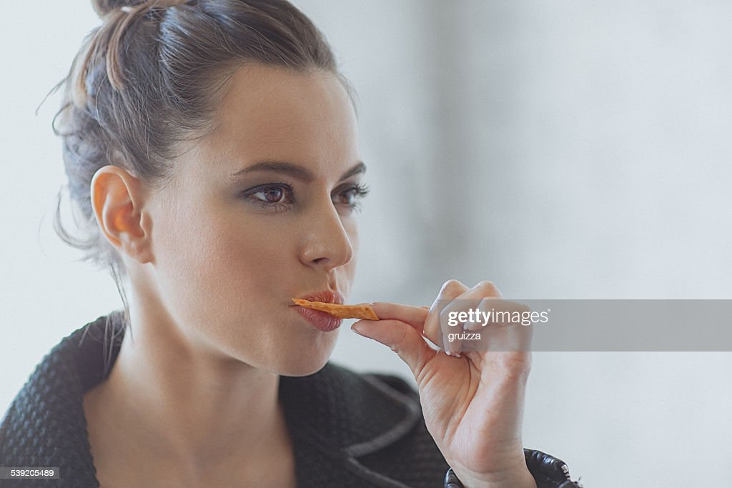 Beautiful young woman eating muesli bar snack