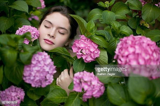 Beautiful young woman embracing hydrangea plant