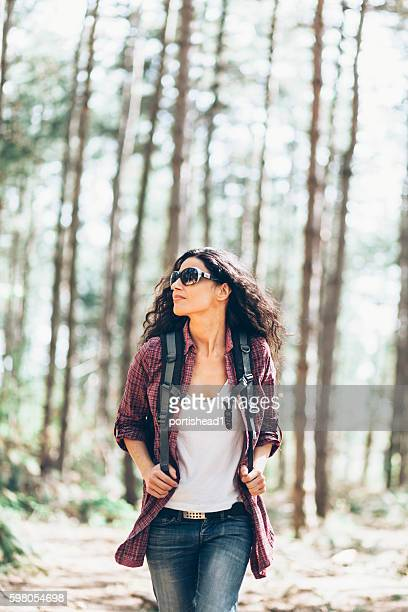 Beautiful young woman enjoying forest hiking