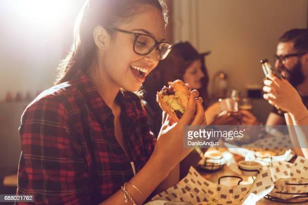 belle jeune femme appréciant son burger