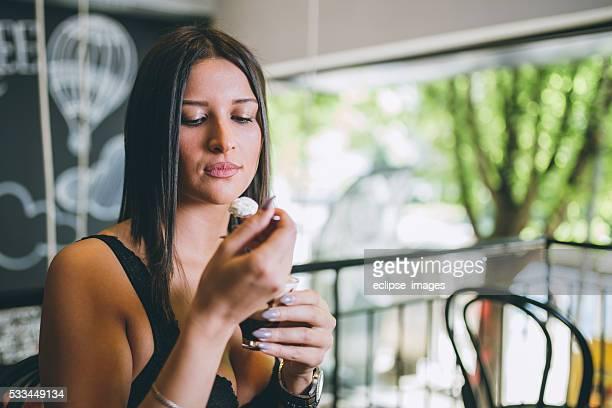 Beautiful young woman enjoying hot chocolate in cafe