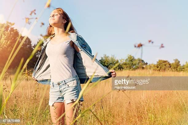 美しい若い女性の自然の小麦のフィールドをお楽しみいただけます。