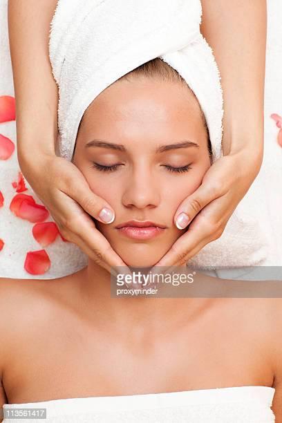 Belle jeune femme se massage du visage de femme les mains