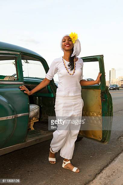 Beautiful young woman getting out of vintage car, Havana, Cuba