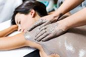 Portrait of beautiful young woman having clay body mask apply by beautician. Detox ritual.