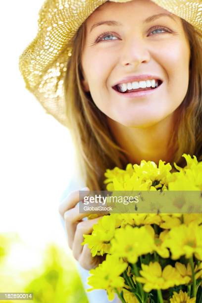 Beautiful young woman holding a bunch of flowers