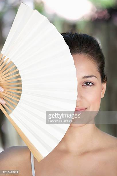 Beautiful young woman holding a Chinese fan in front of her face