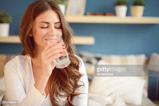 Jolie jeune femme tenant un verre de l'eau