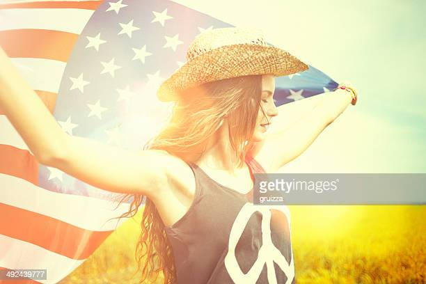 Beautiful young woman holding american flag in the wheat field
