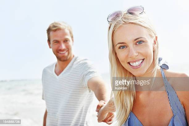 Beautiful, young woman holding boyfriend`s hand on the beach
