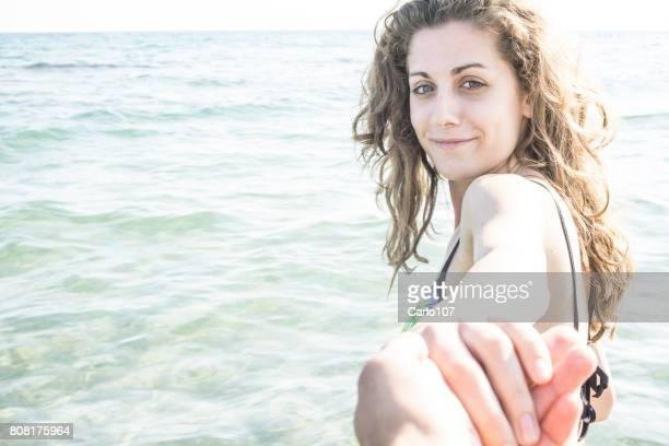 Beautiful young woman holding her boyfriend's hand on the beach