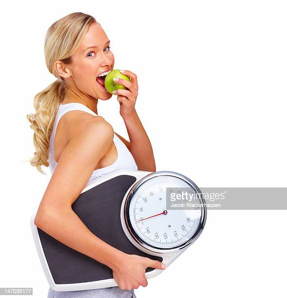 Beautiful young woman holding measuring instrument and eating an apple