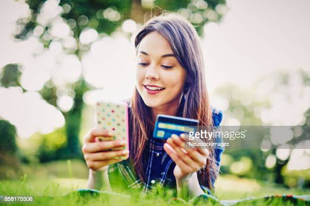 Beautiful young woman holding smart phone and credit card in park
