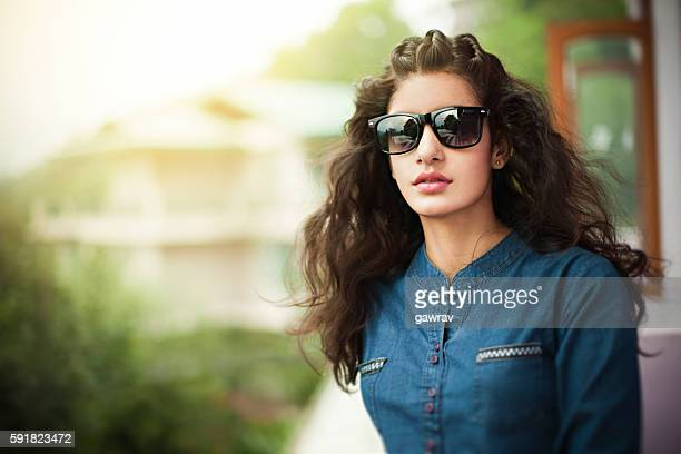Beautiful young woman in balcony looking at view through sunglasses.