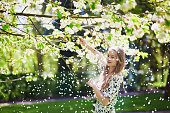 Beautiful young woman enjoying sunny spring day in park during cherry blossom season
